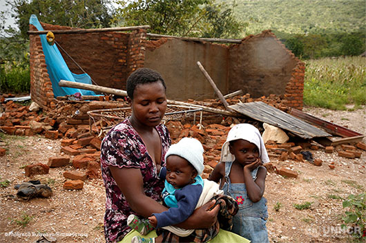 Nomatter Ncube and her kids sit beside their washed away family home in Zimbabwe following Cyclone Idai.