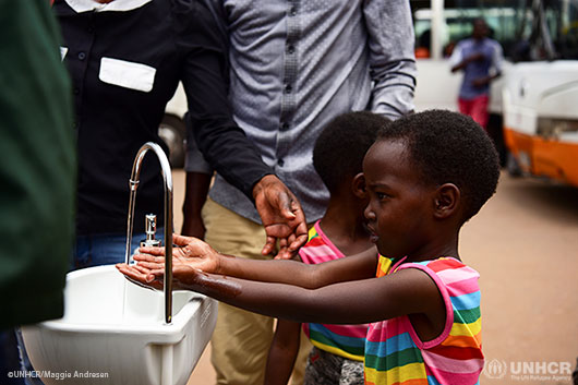 Twin sisters, Emeline and Eveline, wash their hands at a public hand washing station as a cautionary measure against the coronavirus.